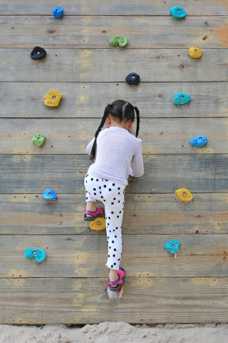 Little child girl trying on free climbing on the playground wooden wall outdoors.